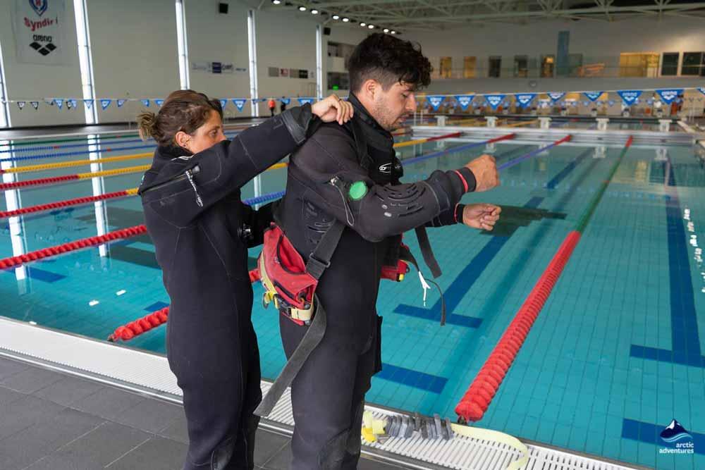 Dive instructor closing dry suit zipper