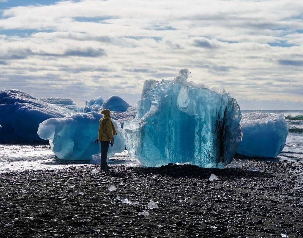 Woman standing next to a glacier at Jokulsarlon Glacier Lagoon