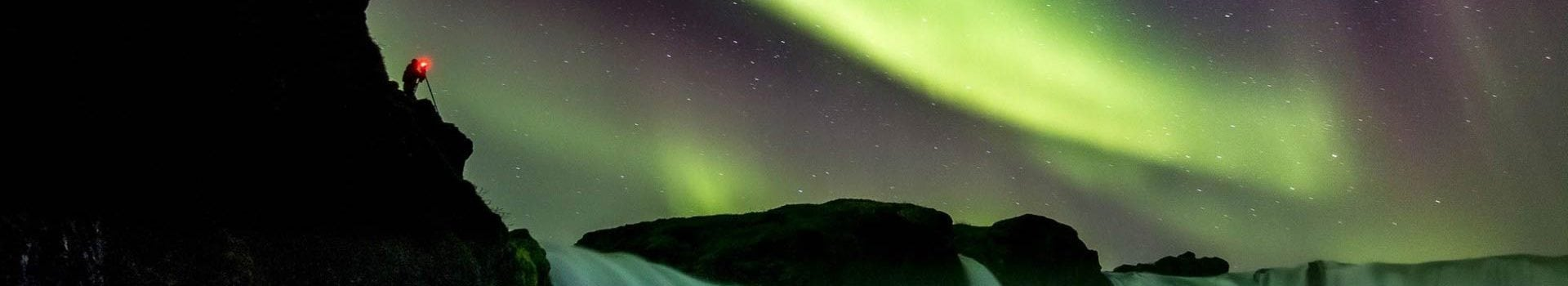 Photographer taking photos of the northern lights in the sky in Akureyri, Iceland