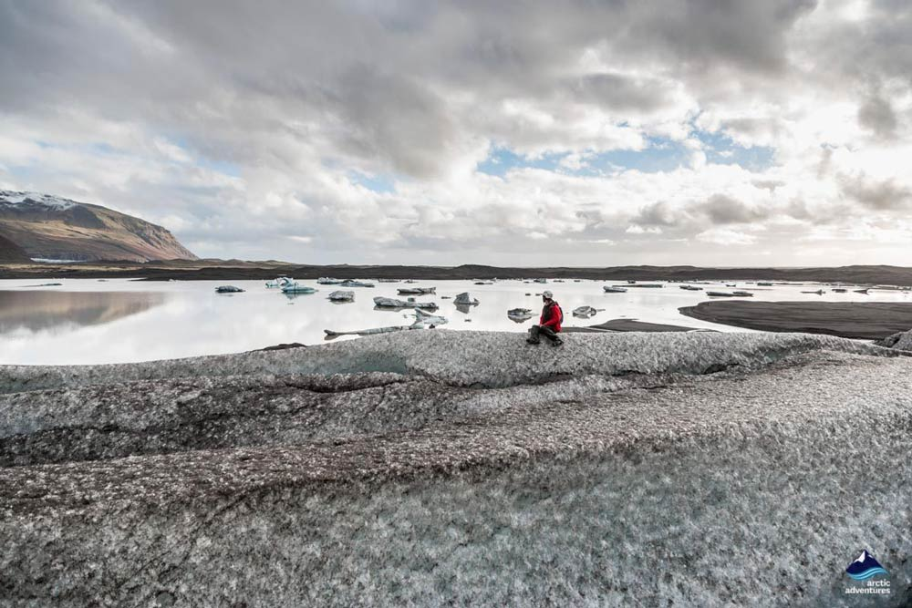 Woman sitting on Skaftafellsjokull Glacier in Iceland