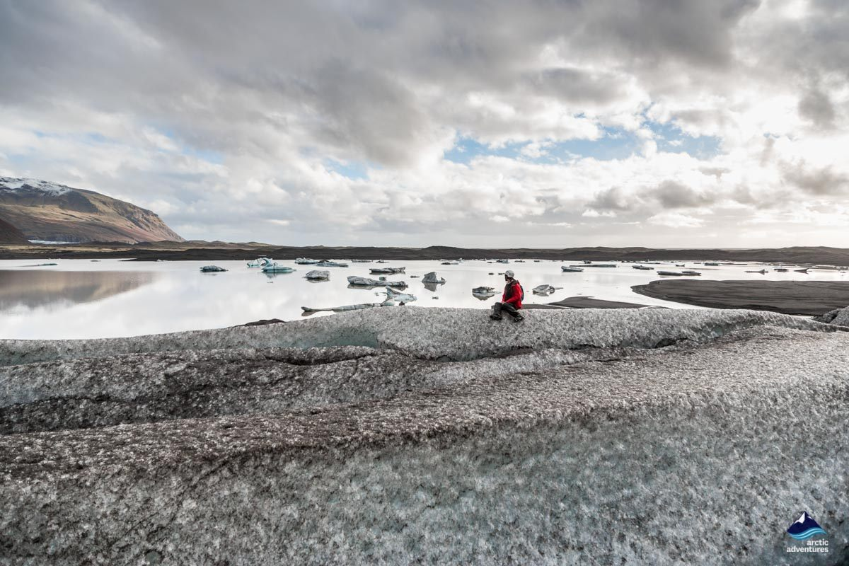 Woman sitting on Skaftafellsjokull Glacier in Iceland