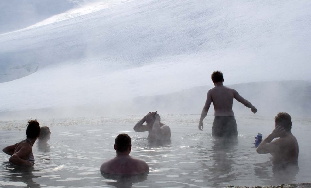 People bathing in Strútslaug Pool in the Highlands