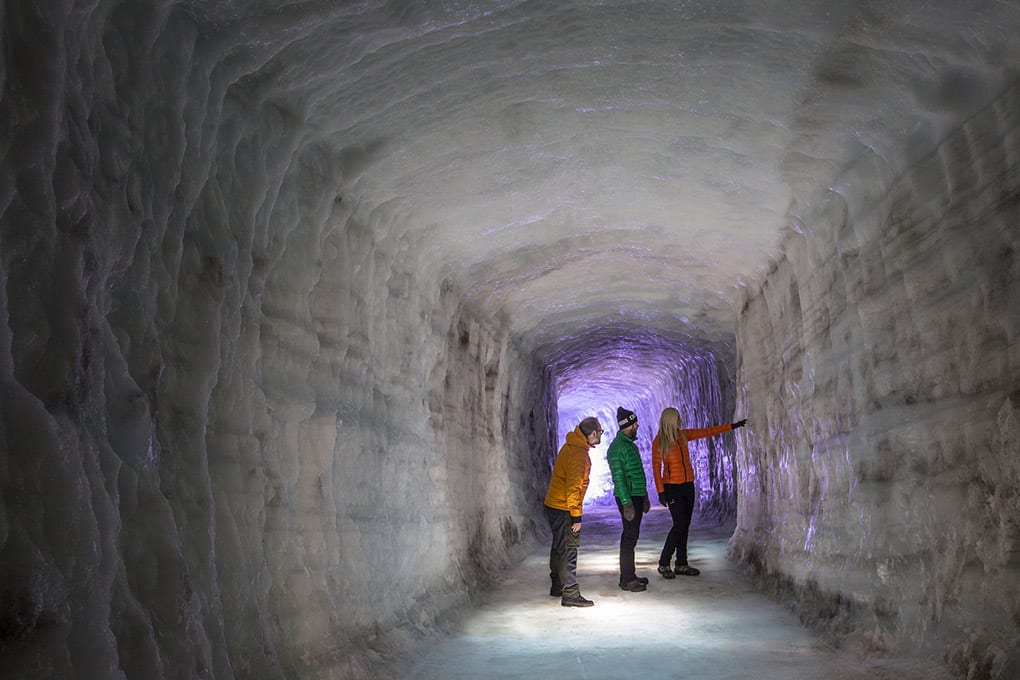 People exploring walls inside Into the Glacier ice cave