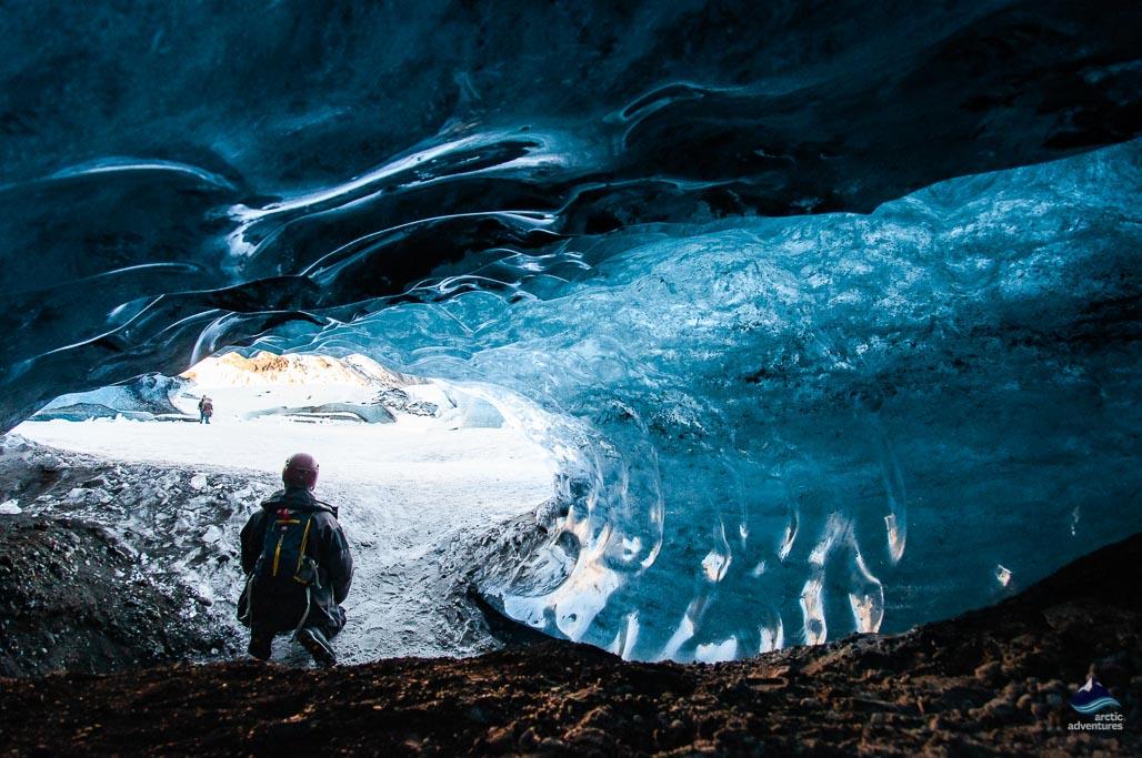 导游蹲在蓝冰洞口拍照