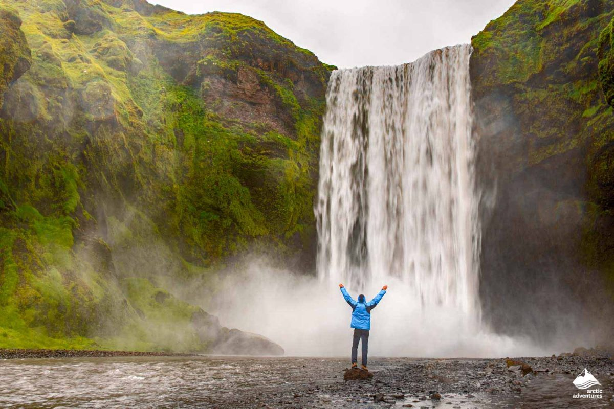Single man standing near Skogafoss waterfall in Iceland and spread his hands. Travel summer nordic concept.
