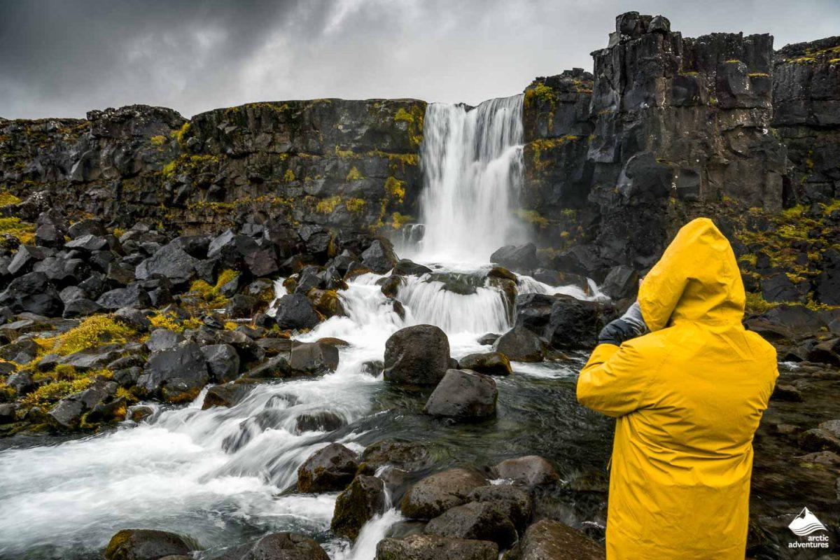 Tourist in gelber Regenjacke vor Oxararfoss Wasserfall