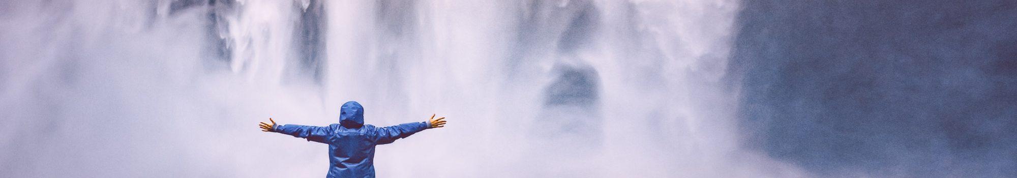 Man raised hands near waterfall