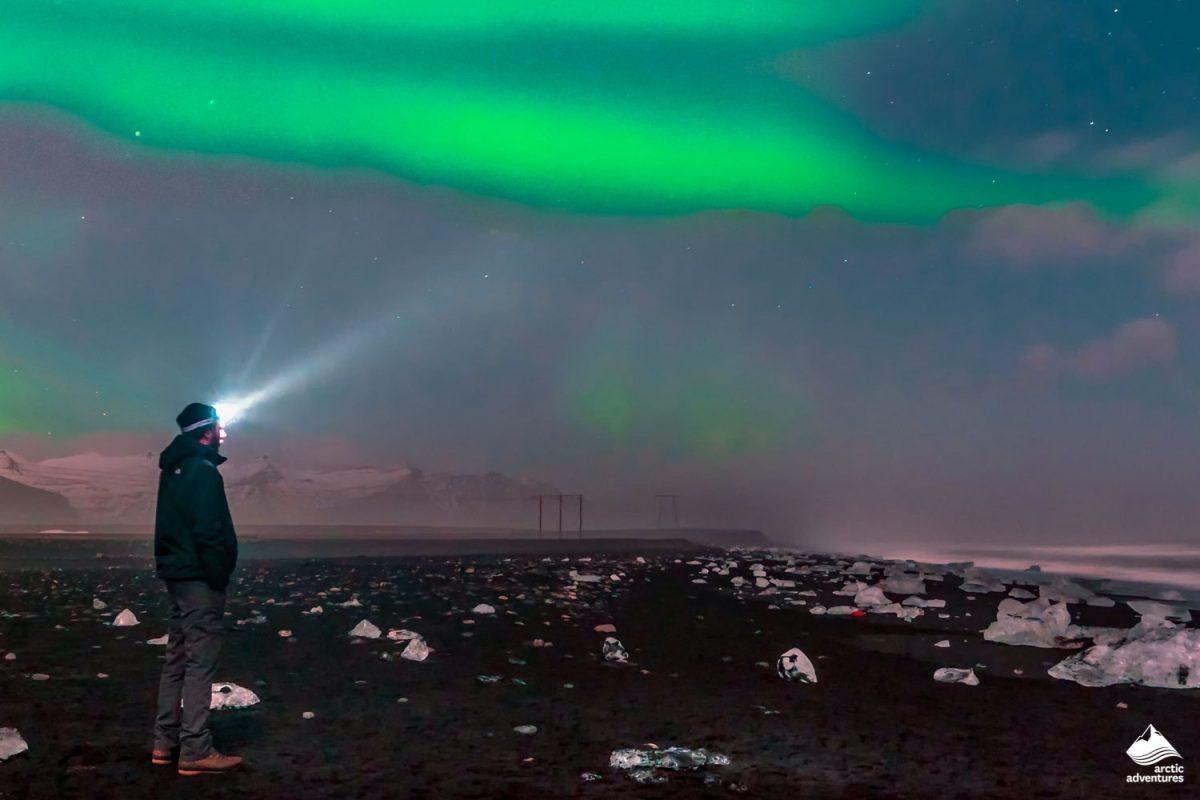 Man admiring Aurora Borealis on the Diamond beach