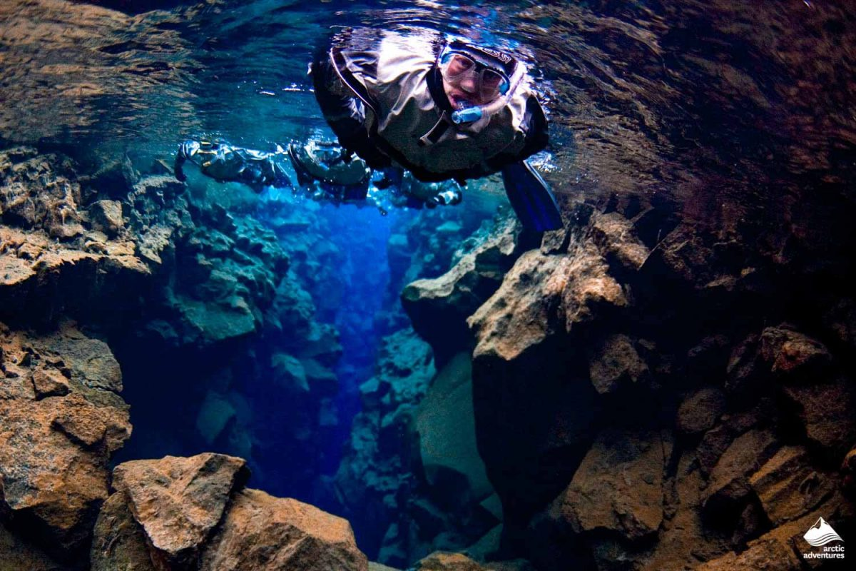 People diving in blue and clear Silfra Fissure