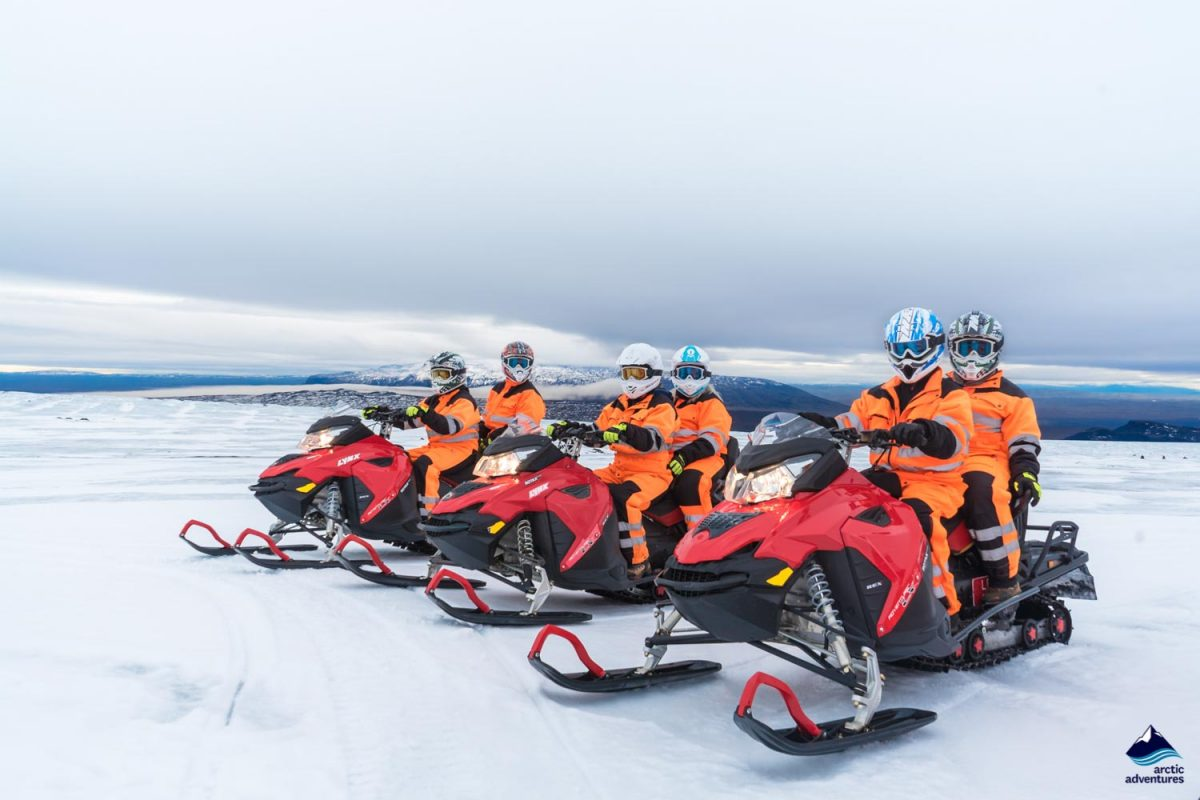 Snowmobilers standing in a row on a Langjokull glacier