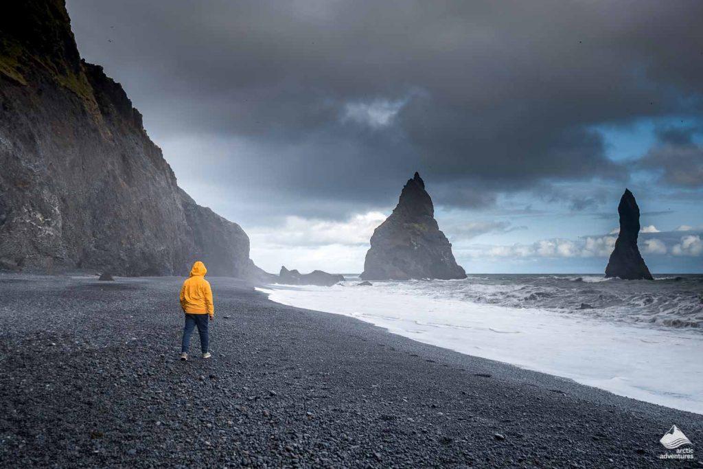 Man walking on Reynisfjara black sand beach