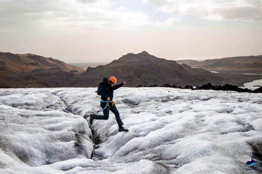 Guy jumping over small stream on Solheimajokull glacier