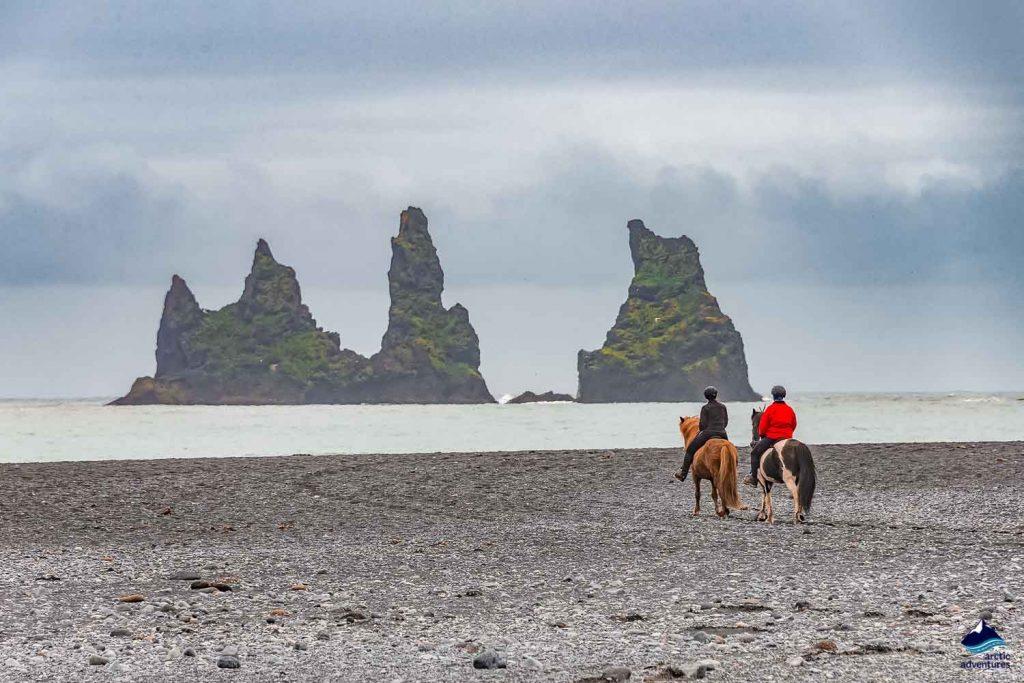 Two lonely horse riders on black sand beach near Reynisdrangar stacks