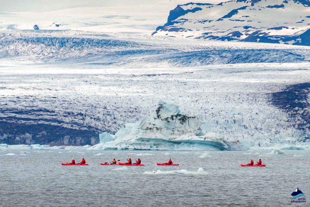 A group of friends in red kayaks near the Jökulsárlón glacier