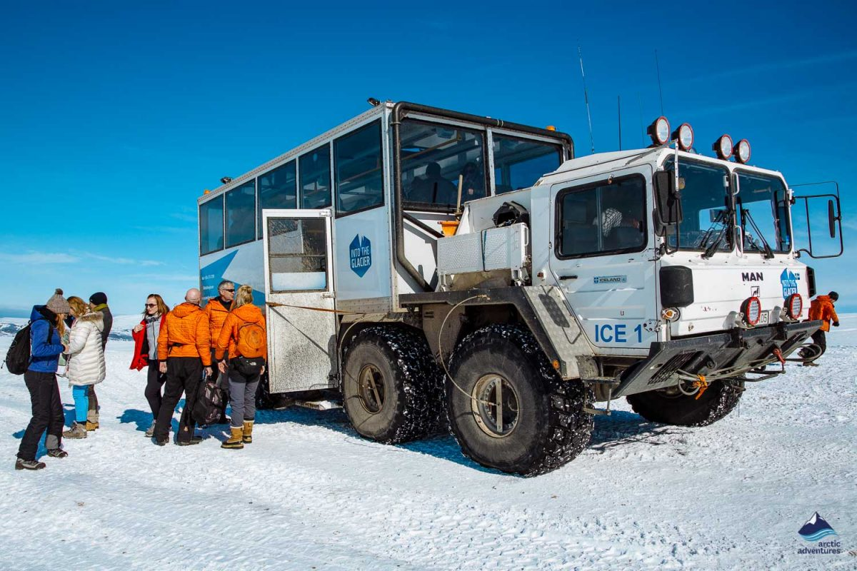 People standing near the Into the Glacier truck in Iceland