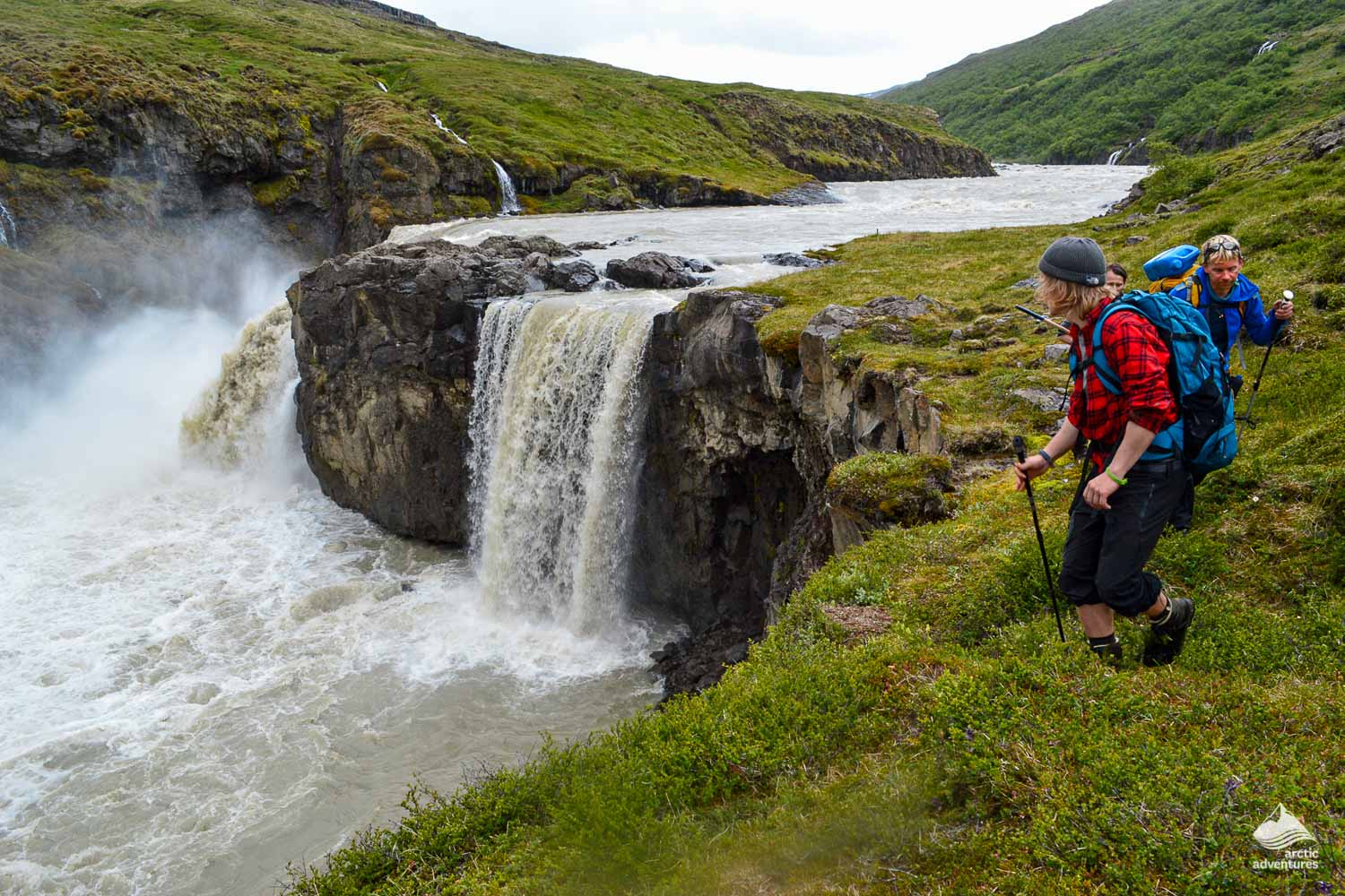 People hiking near waterfall in Iceland