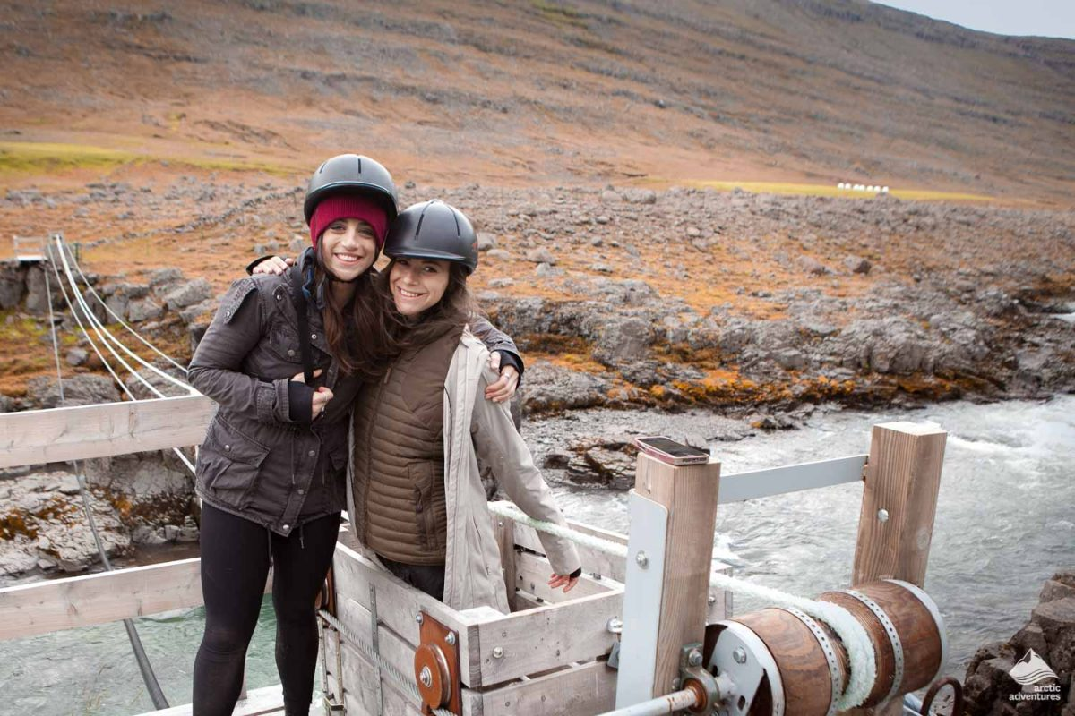 Two girls uses cable ferry to cross river in Iceland
