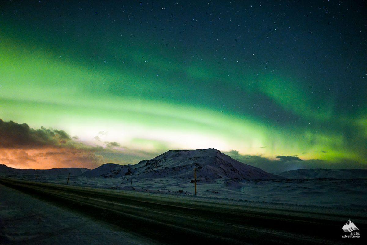 Icelanding road across Aurora Borealis