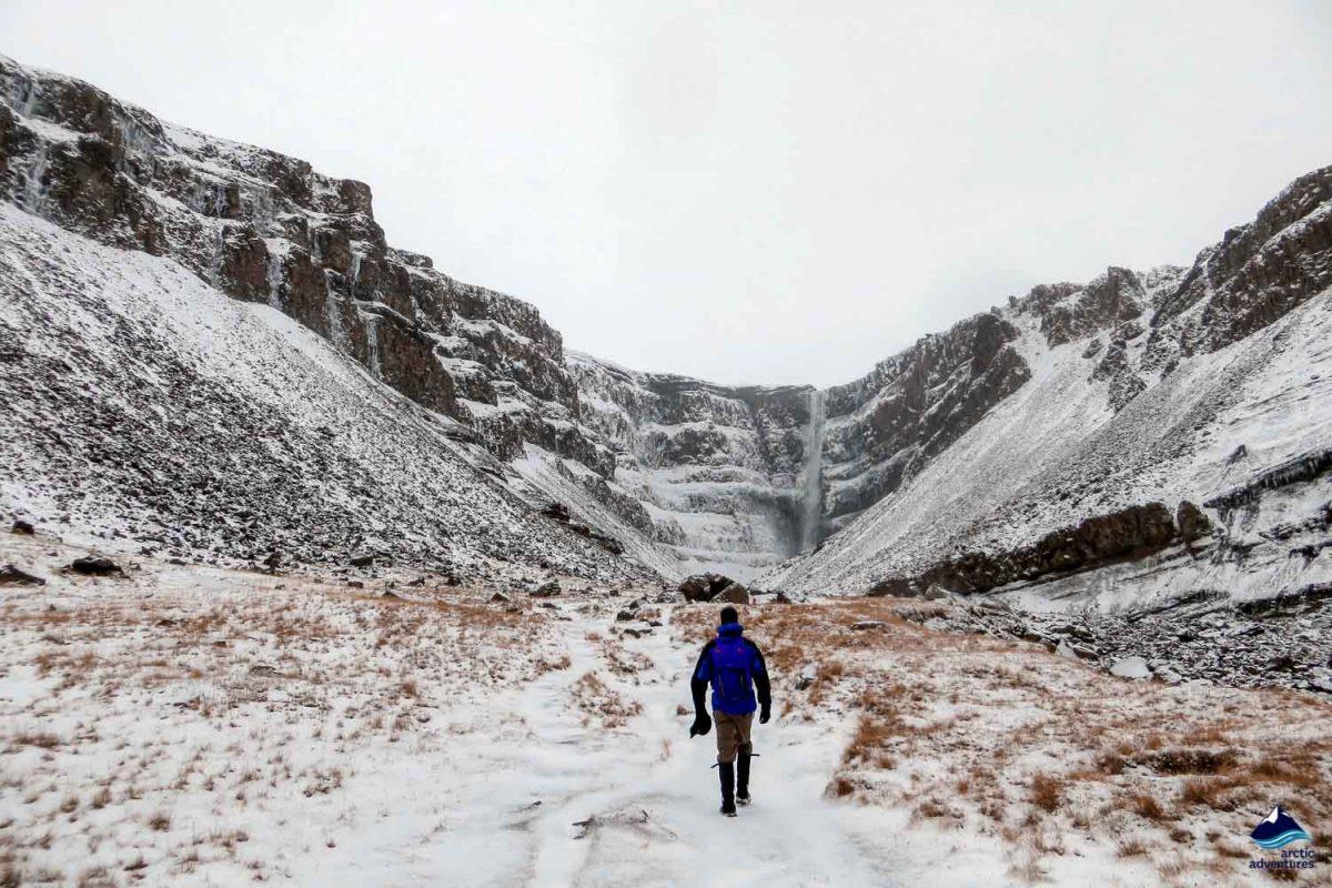 Man heading towards Hengifoss Waterfall in Iceland