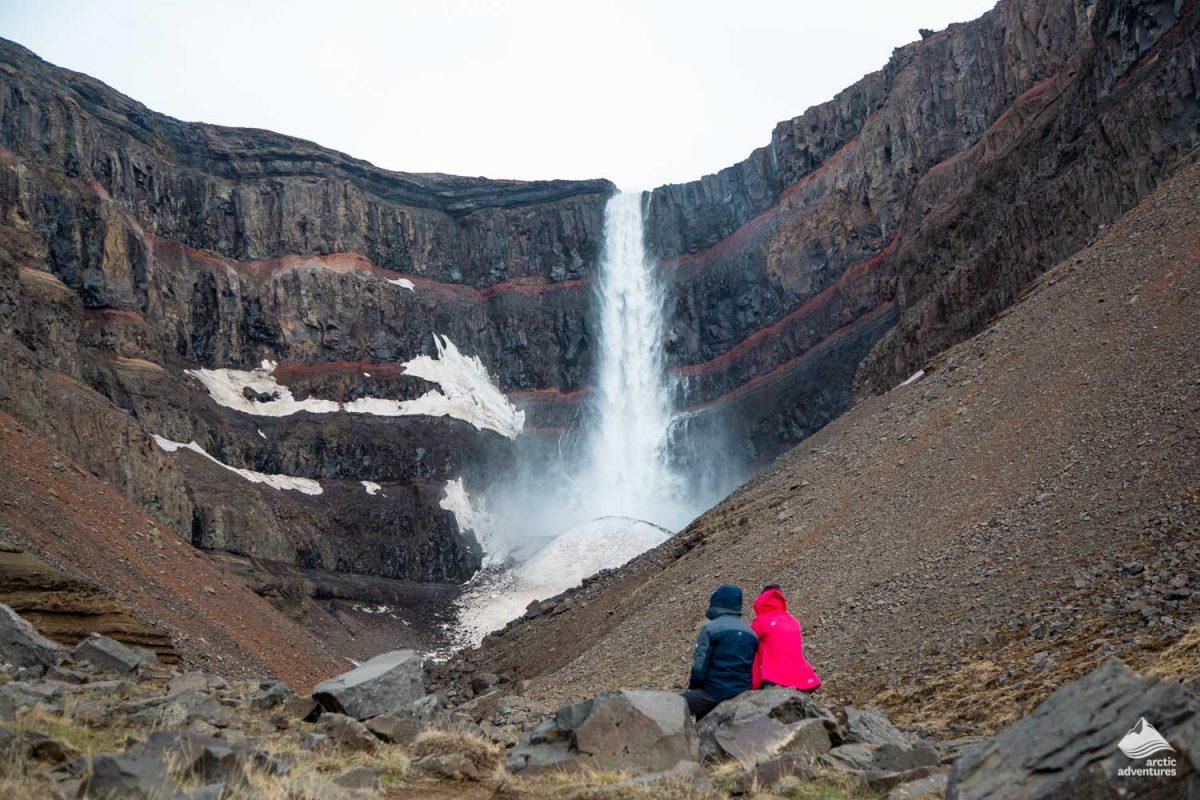 Couple looking at Hengifoss waterfall