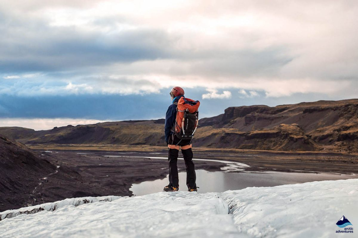 Man standing at the edge of a mountain in Solheimajokull
