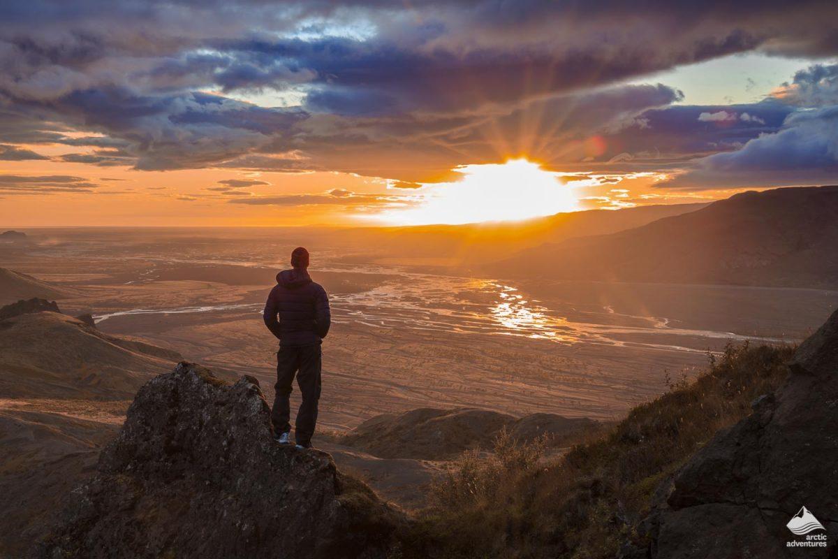 Man silhouette standing at the edge of mountain enjoying sunset