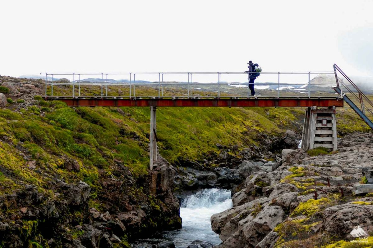 Man crossing the wooden bridge at Fimmvorduhals mountain