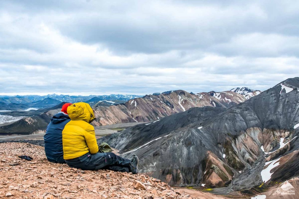 Couple sitting and looking an the Blahnukur volcano in Iceland