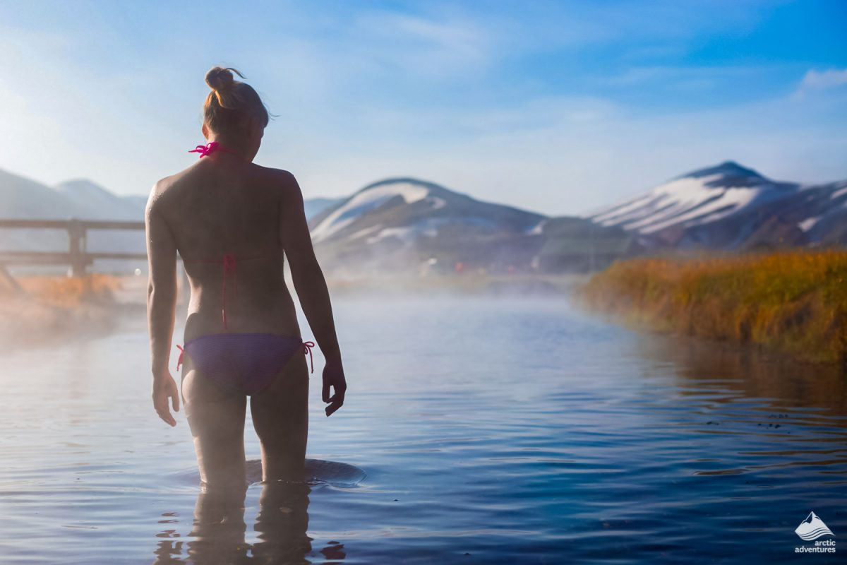 Young woman relax in a hot spring in Iceland
