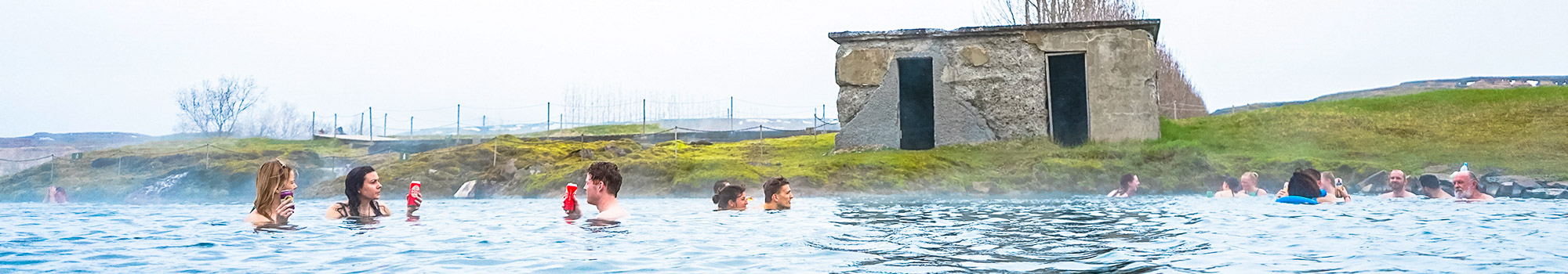 People bathing in Secret Lagoon in South of Iceland
